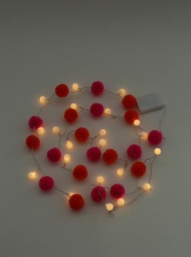 Oranžovo-rúžová svietiaca reťaz s bambuľami Disaster Pom Pom