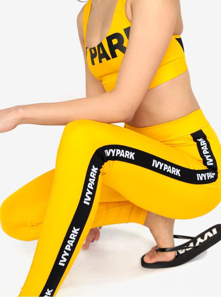 Žluté legíny s černým pruhem na nohavicích Ivy Park